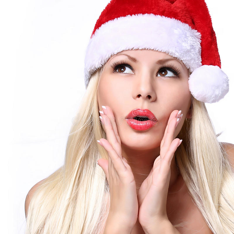 圣诞节妇女。圣诞老人帽子的惊奇的美丽的白肤金发的女孩 免版税库存照片