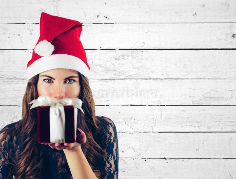 圣诞节妇女在圣诞老人帽子的举行礼物隔绝了画象 白色砖墙背景的微笑的愉快的女孩 库存照片