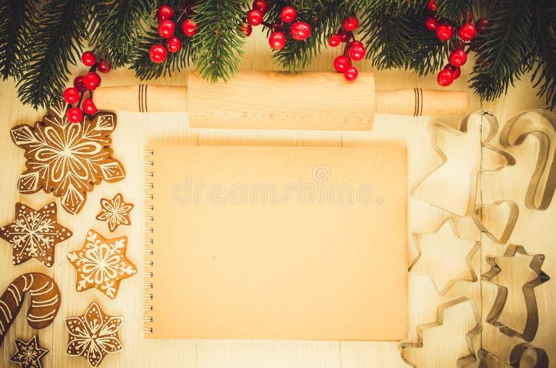 圣诞节姜饼、棕色笔记本、曲奇饼切削刀和滚针 免版税图库摄影