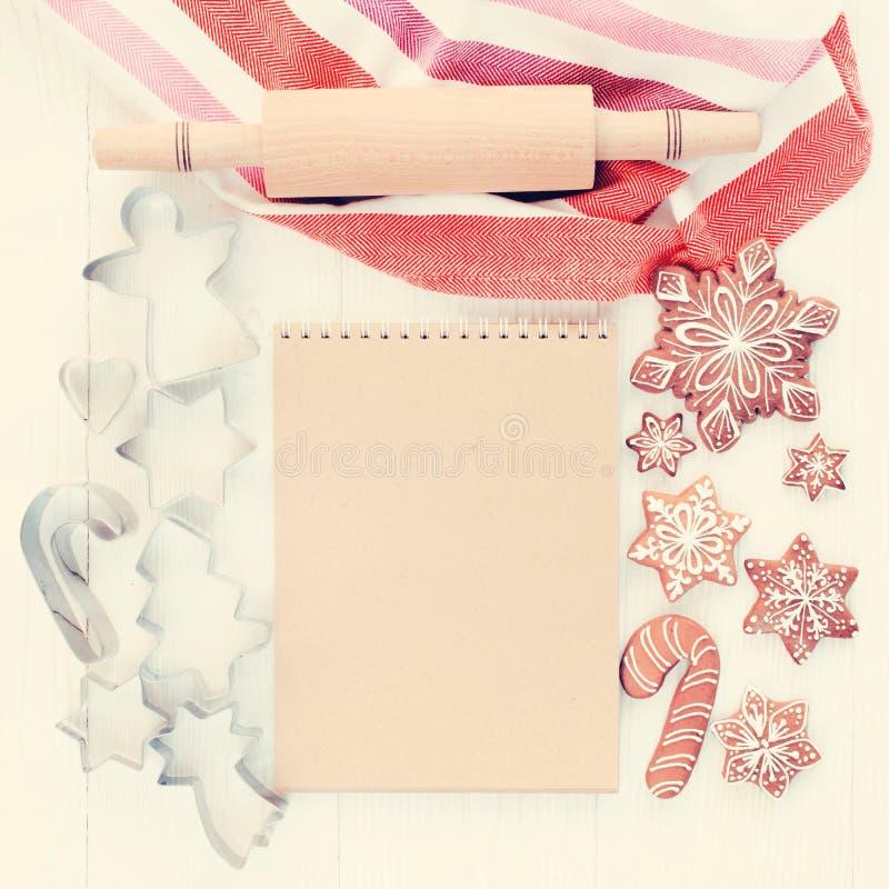 圣诞节姜饼、棕色笔记本、曲奇饼切削刀和滚针 免版税库存图片