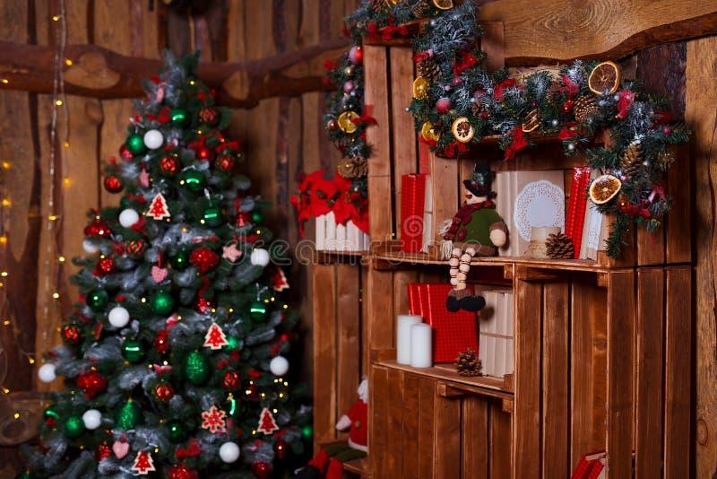 圣诞节室室内设计、光装饰的Xmas树,礼物、礼物、玩具、蜡烛和诗歌选照明设备 免版税库存图片