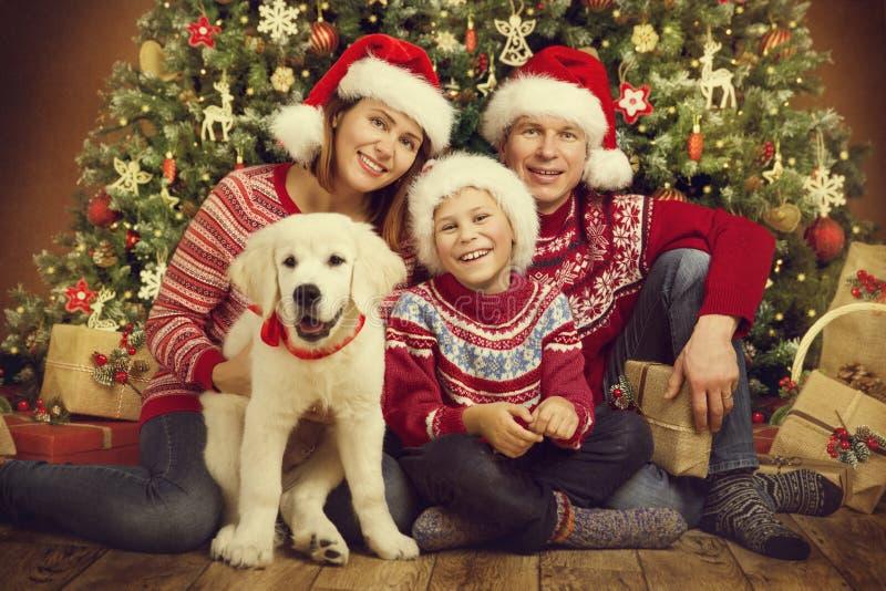 圣诞节家庭和狗在Xmas树,愉快的母亲父亲儿童画象下在红色帽子 免版税库存照片