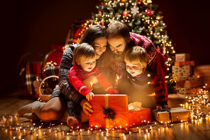圣诞节家庭开放点燃的当前礼物盒在Xmas树,愉快的母亲父亲孩子下 免版税库存图片