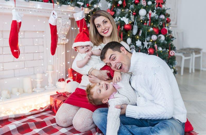 圣诞节家庭特写镜头画象 有一个新出生的女婴和爸爸的妈妈有儿子的 免版税库存照片