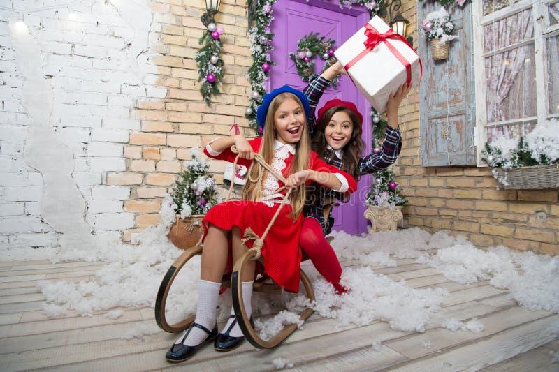 圣诞节已经在这里 女孩sledding与圣诞礼物箱子 小逗人喜爱的女孩接受了节日礼物 少许孩子 库存图片