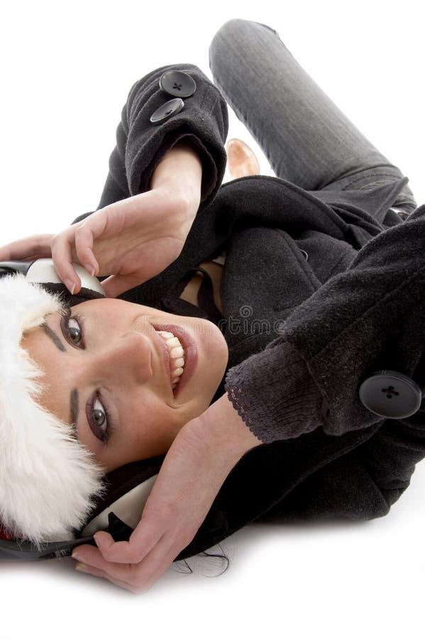 圣诞节帽子听的音乐佩带的妇女 库存照片