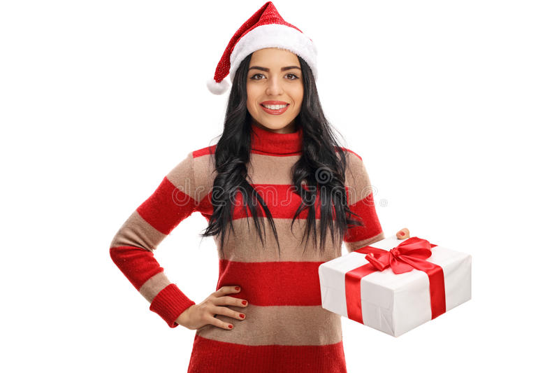 戴圣诞节帽子和拿着礼物的愉快的妇女 库存照片
