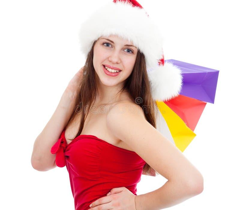 圣诞节帽子的俏丽的女孩与五颜六色的袋子 库存照片
