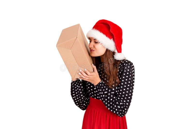 圣诞节帽子的失望的女孩在她的手上的拿着一件大礼物 背景查出的白色 节假日概念 免版税库存照片
