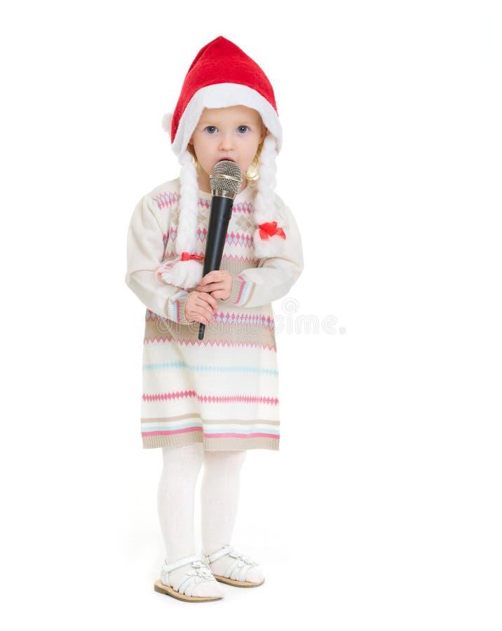圣诞节帽子的女婴使用话筒 免版税库存图片