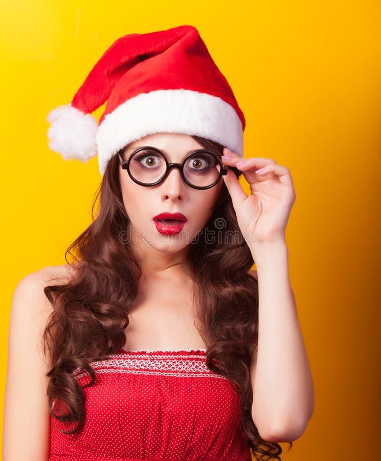 圣诞节帽子的女孩有玻璃的 免版税库存图片