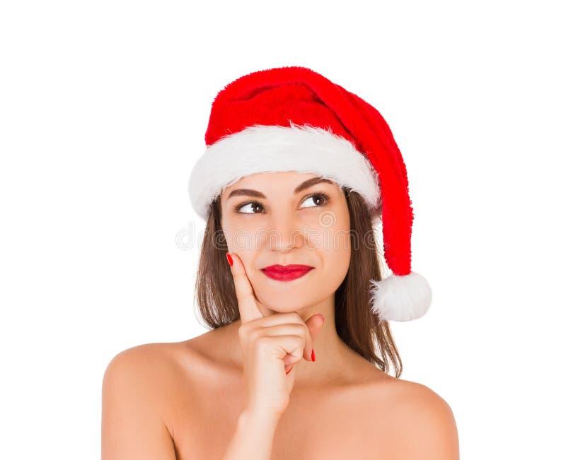 圣诞节帽子的想法的和反射的女孩 在白色背景隔绝的红色圣诞老人帽子的情感妇女 愉快的基督 免版税库存照片
