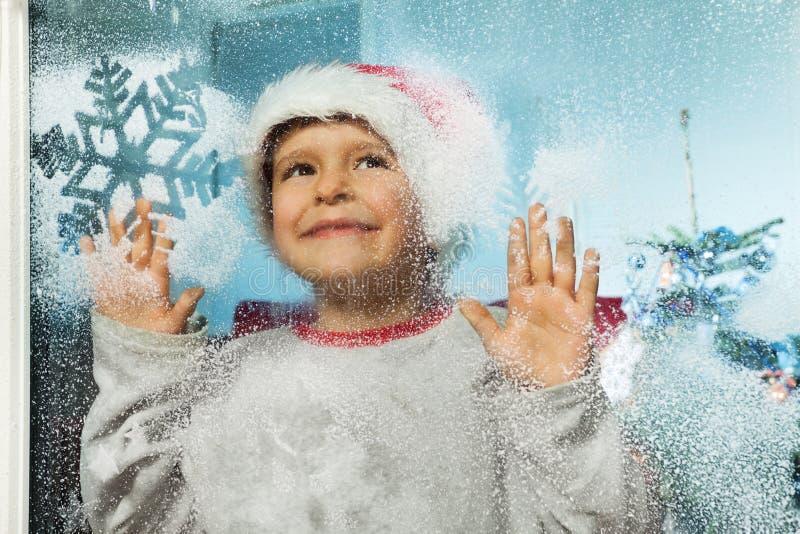 圣诞节帽子的男孩在与snoflakes的窗口后 免版税图库摄影