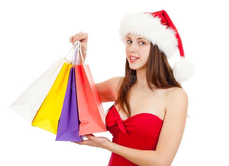 圣诞节帽子的秀丽女孩与五颜六色的袋子 库存照片