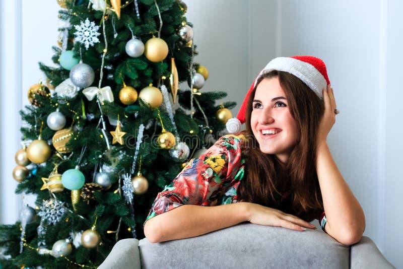 圣诞节帽子的美丽的女孩在圣诞树旁边 图库摄影