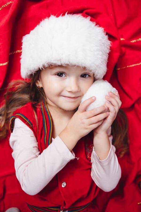 圣诞节帽子的逗人喜爱的女孩在红色背景 免版税库存图片