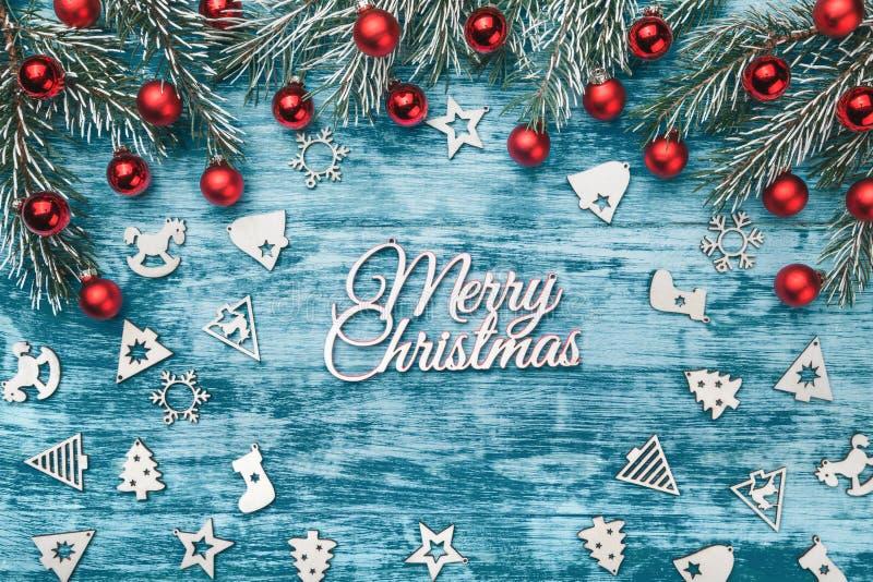 圣诞节快活的主题 与木被装饰的玩具、冷杉分支和红色装饰球的Xmas和新年快乐构成 库存图片