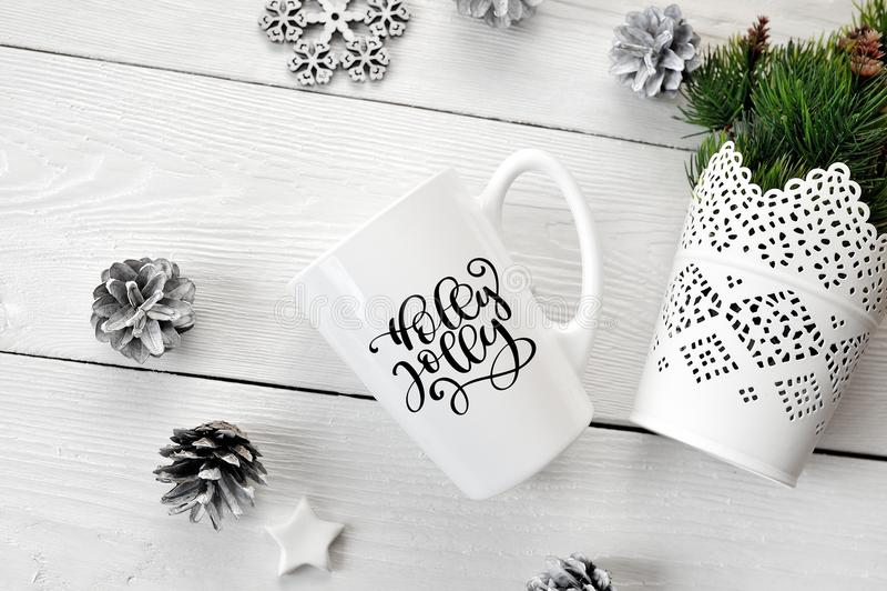 圣诞节愉快地文本霍莉在有圣诞节装饰的一个白色杯子 平的位置,顶视图照片大模型 免版税图库摄影