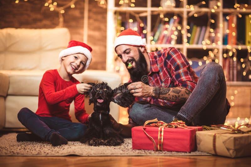 圣诞节愉快的男孩和父亲有小狗的 库存照片