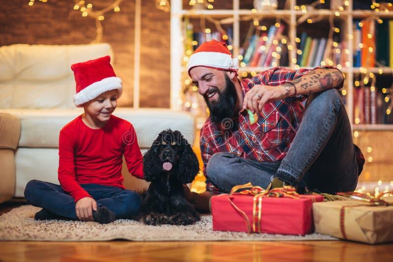 圣诞节愉快的男孩和父亲有小狗的 免版税库存图片
