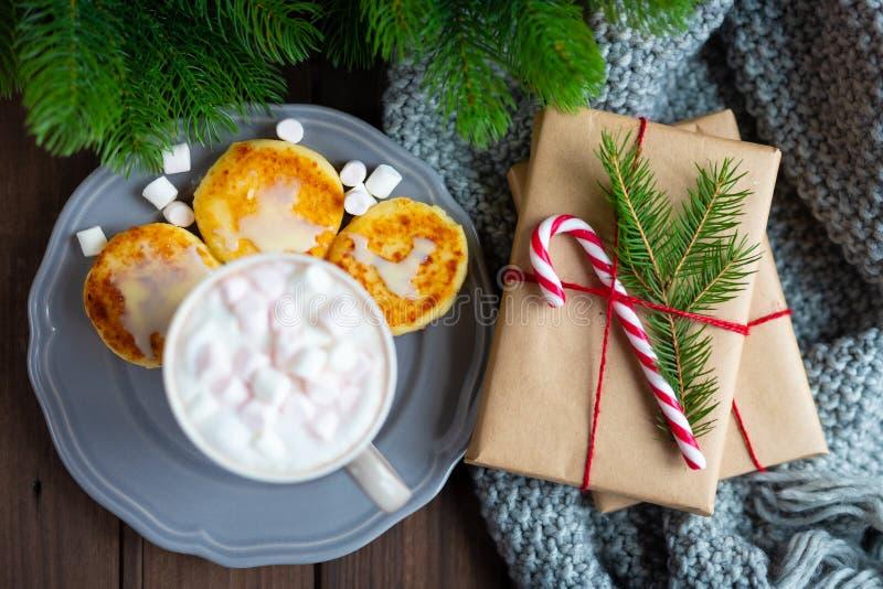 圣诞节或新年与杯子咖啡的早晨早餐恶巧克力热饮用蛋白软糖和乳酪薄煎饼 免版税图库摄影