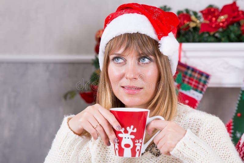 圣诞节或新年庆祝 关闭杯子射击在妇女的手上有热的饮料的在圣诞树背景,愉快的holid 免版税库存图片