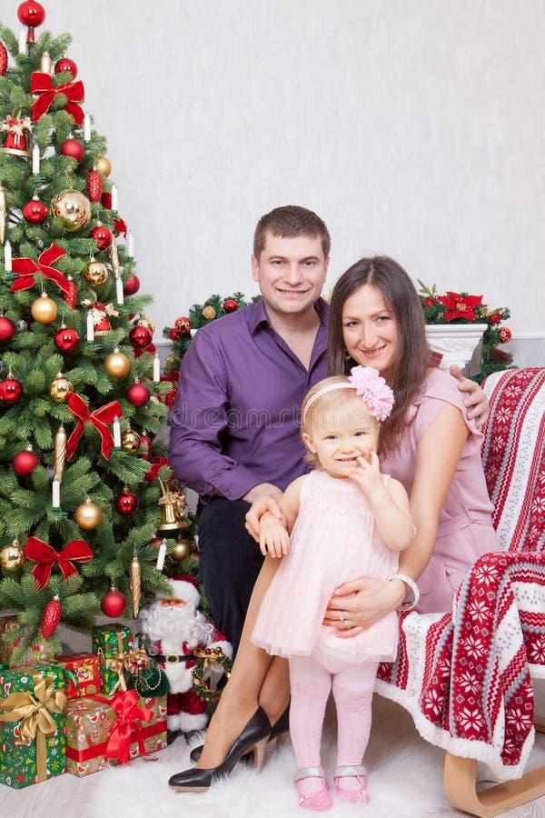 圣诞节或新年庆祝 坐在椅子的愉快的年轻家庭在与xmas礼物的圣诞树附近 与克里斯的一个壁炉 库存照片