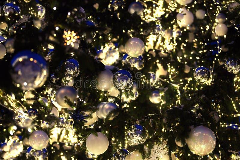 圣诞节或新年弄脏了bokeh背景,银色的圣诞装饰,并且在绿色杉木分支的白色球关闭  库存图片