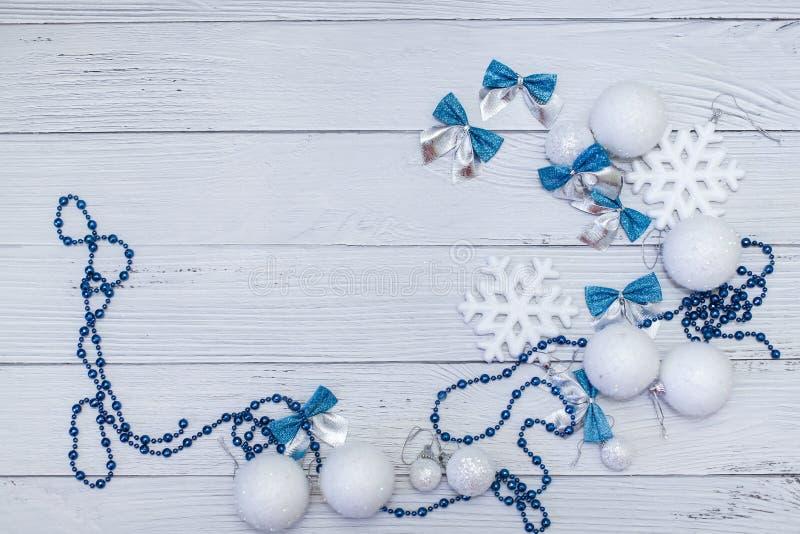 圣诞节或新年构成在银色白色和蓝色颜色与球雪花在白色木头鞠躬并且成串珠状 图库摄影