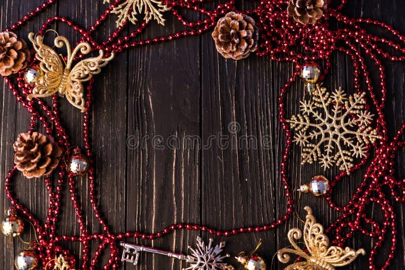 圣诞节或新年框架 圣诞节分支、冷杉球果和红色项链在木板 库存图片