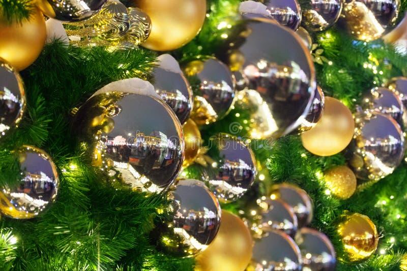 圣诞节或新年欢乐背景、金黄xmas的装饰和银色球,在绿色杉木分支的发光的光关闭  免版税库存图片