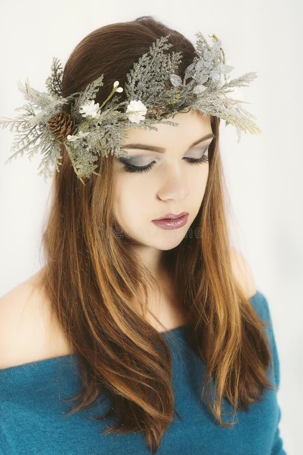 圣诞节或新年秀丽在白色背景隔绝的妇女画象 有佩带的圣诞节花圈少妇在她的头 库存照片