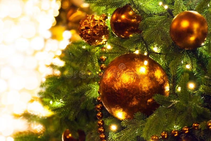 圣诞节或新年贺卡、金黄圣诞装饰玻璃球在绿色杉木分支,白雪和发光的光 免版税库存照片