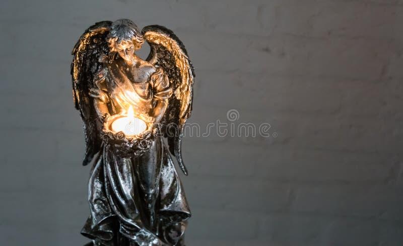 圣诞节或精神传统,拿着灼烧的光的一个银色天使雕塑 库存图片