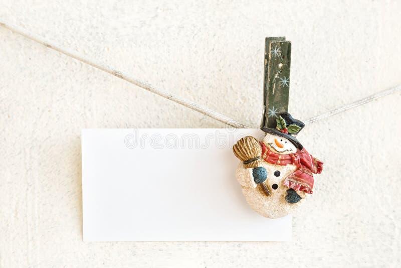 圣诞节拿着白皮书卡片的雪人晒衣夹 图库摄影
