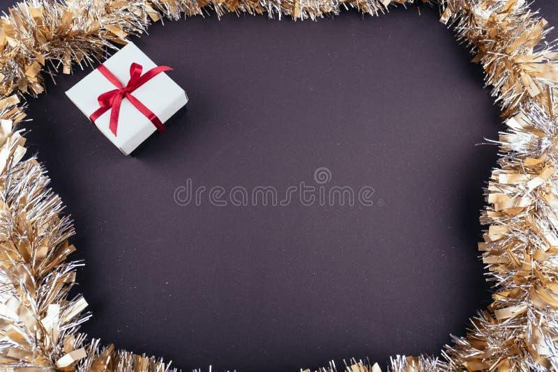 圣诞节新年假日黑暗的背景红色礼物盒装饰品诗歌选闪亮金属片从上面 免版税库存图片