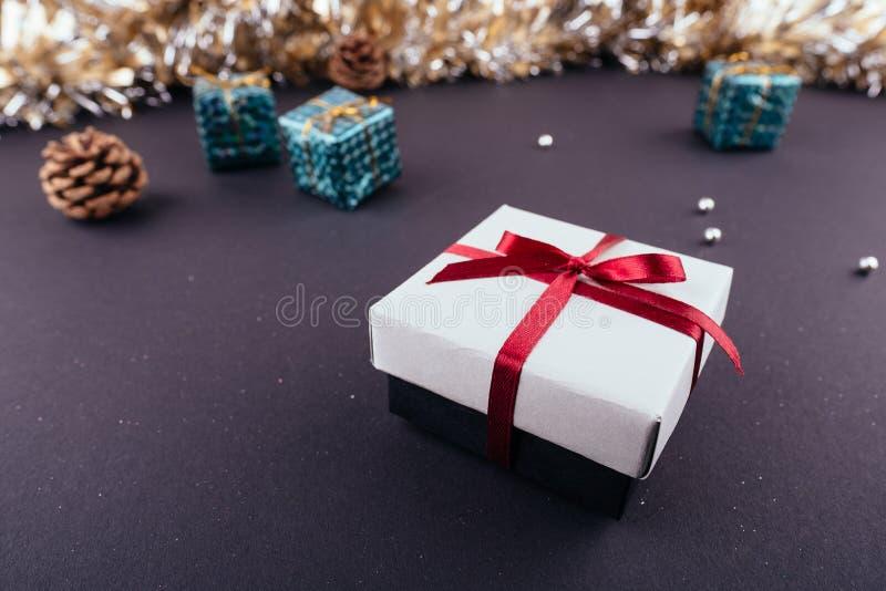 圣诞节新年假日黑暗的背景红色礼物盒装饰品诗歌选闪亮金属片从上面 免版税库存照片