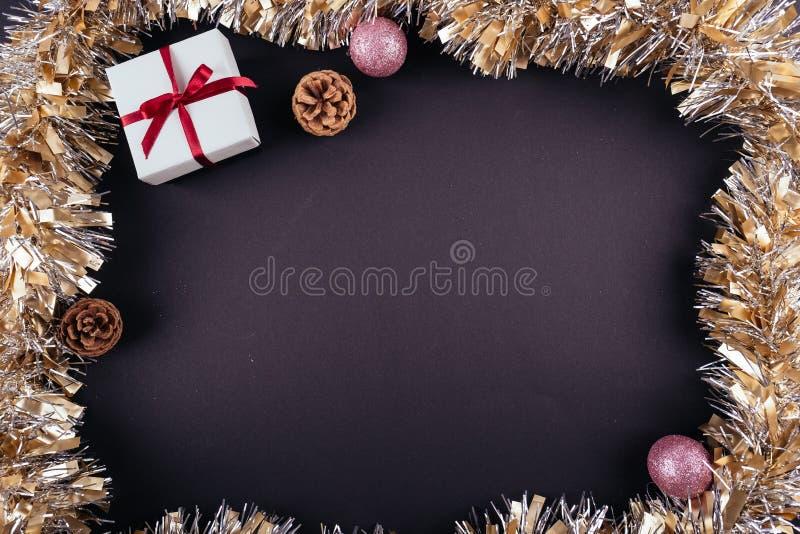 圣诞节新年假日黑暗的背景红色礼物盒装饰品诗歌选闪亮金属片从上面 库存照片