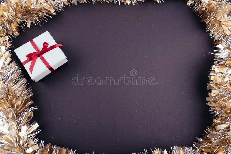 圣诞节新年假日黑暗的背景红色礼物盒装饰品诗歌选闪亮金属片从上面 免版税图库摄影