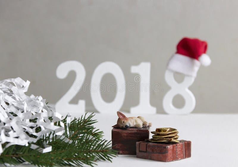 圣诞节新年睡觉在有礼物的箱子的狗小狗在冷杉附近 免版税图库摄影