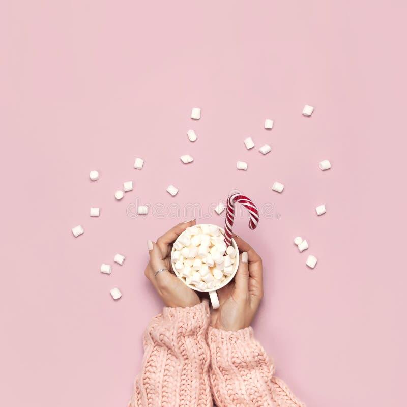 圣诞节新年饮料,白色杯子用蛋白软糖在女性手上在被编织的毛线衣和棒棒糖在桃红色背景上面 免版税图库摄影