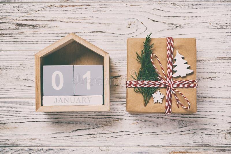 圣诞节日历1月1日 圣诞礼物,在葡萄酒,被定调子的木白色背景的冷杉分支 复制空间,顶视图 库存照片