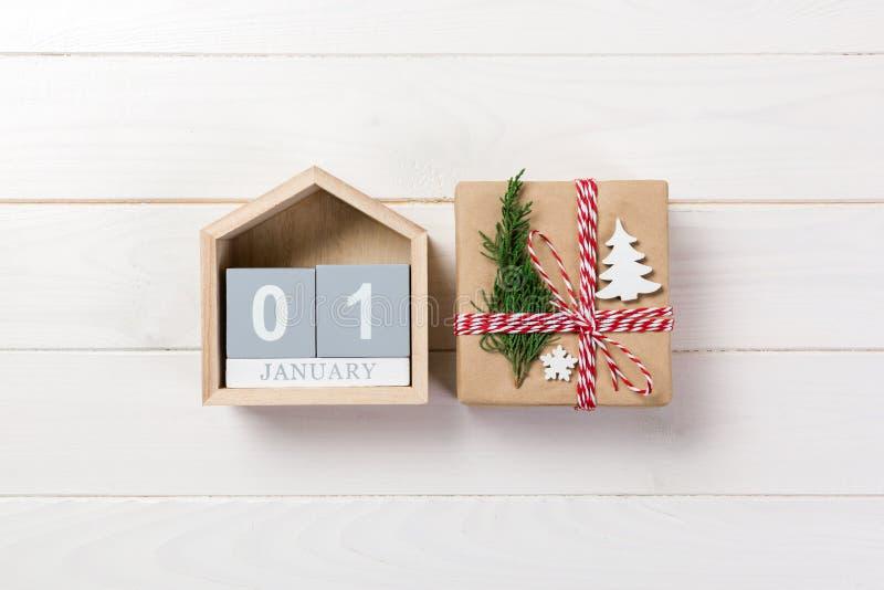 圣诞节日历1月1日 圣诞节礼物,冷杉在木白色背景分支 复制空间,顶视图 库存图片