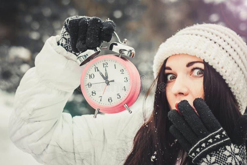 圣诞节时间和新年` s前夕概念 拿着闹钟和指向它的微笑的惊奇的妇女 免版税库存图片
