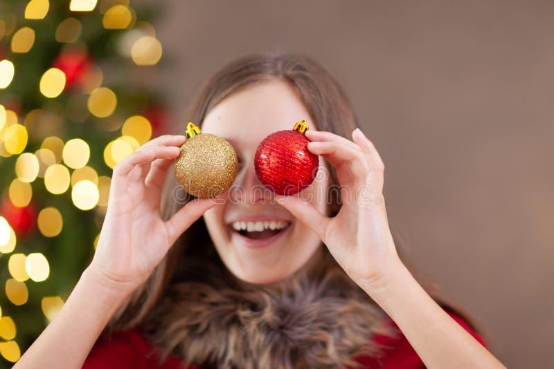 圣诞节时间,有圣诞节球的十几岁的女孩 免版税库存照片