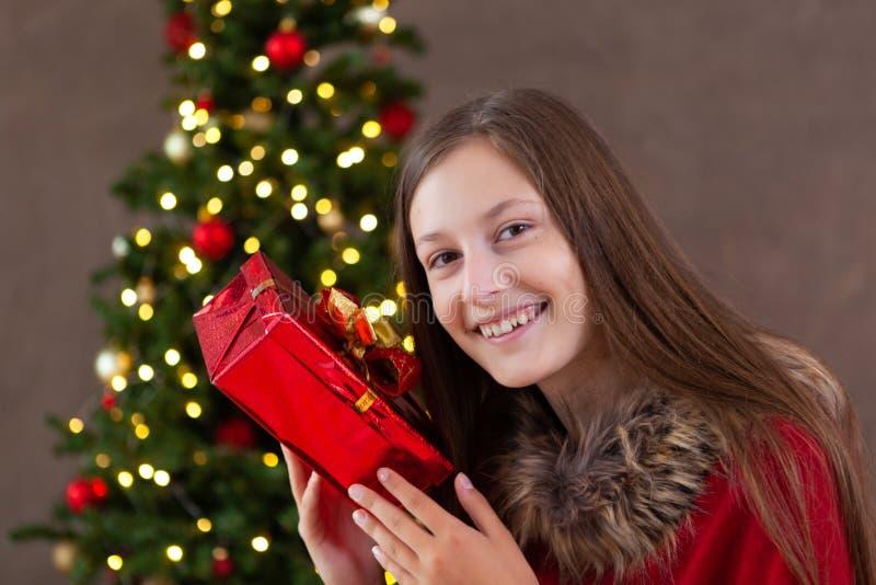 圣诞节时间,有圣诞节礼物的十几岁的女孩 库存图片