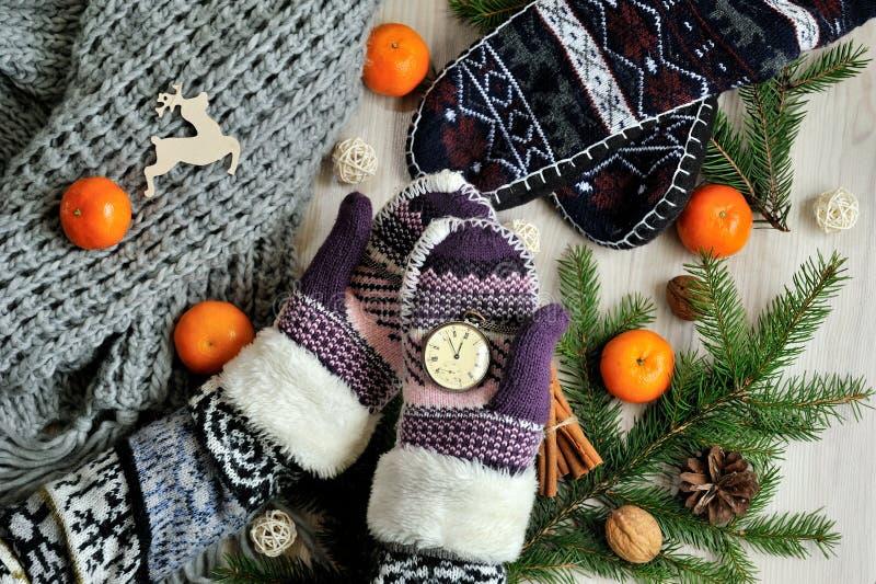 圣诞节时间,时钟在被编织的手套手上 蜜桔和冷杉分支关闭在土气木背景 免版税库存图片