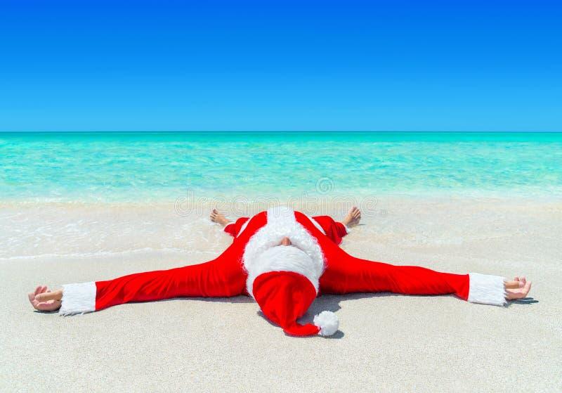 圣诞节晒日光浴在wate的热带海洋海滩的圣诞老人 免版税库存图片