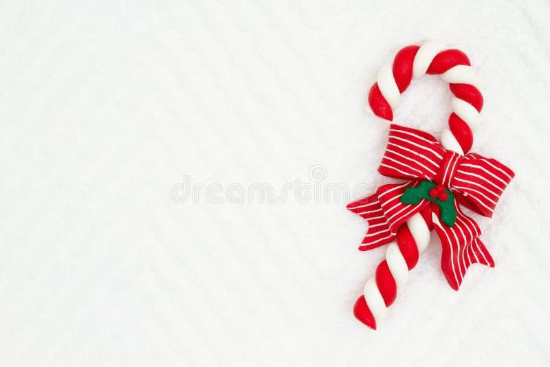 圣诞节有一把弓的棒棒糖在白色V形臂章织地不很细织品背景 免版税图库摄影