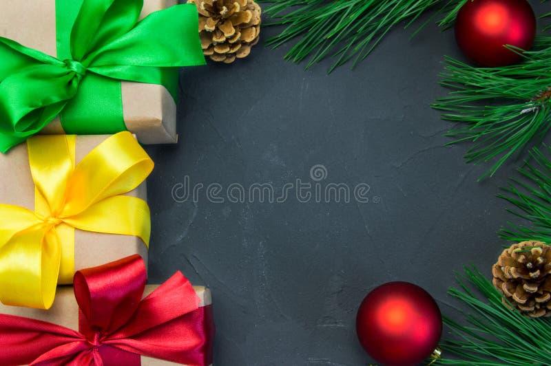 圣诞节有丝带弓的在黑暗的具体背景的礼物盒和分支圣诞树和红色球玩具和锥体 免版税库存照片